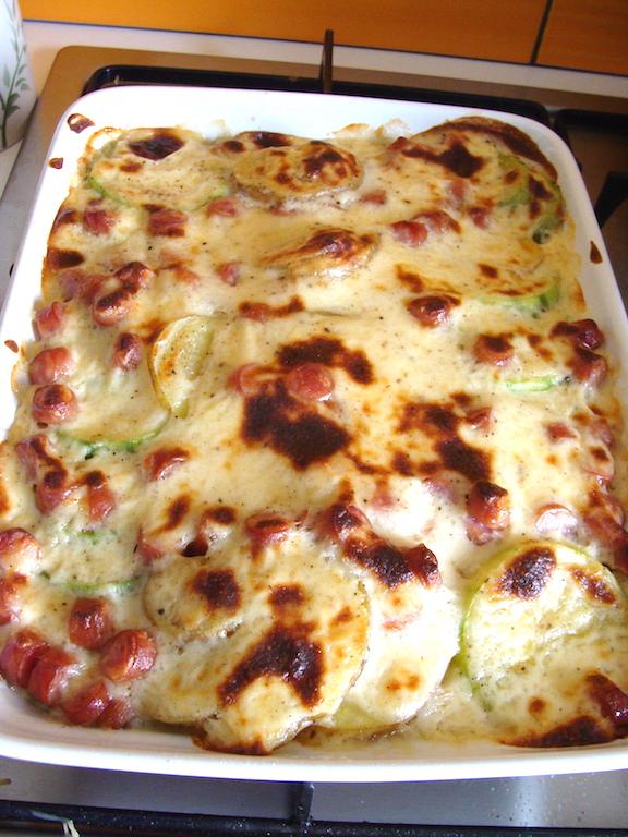 Zapiekanka z cukinii ziemniaków i kiełbasy z sosem Mornay - podana w całości jest apetyczna