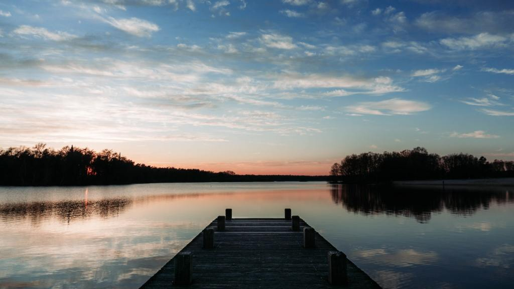 dock on lack at sunrise with forest in background