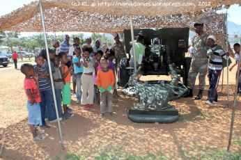 The children form an orderly queue, eagerly waiting for a chance to peer through the sights of the Cape Field Artillery's 25-pounder gun
