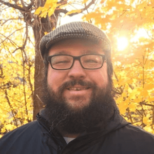 Photo of Elliott Neyme, a white man with dark hair and beard, wearing glasses and a gray hat, smiling in front of trees with yellow leaves. Sunlight is coming through the trees in the background.