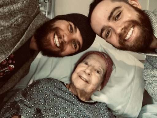 A grandmother in a hospital bed with her two (bearded) grandsons, wearing a winter hat and hospital gown, all three smiling :)