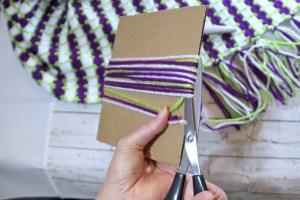 Using scissors cut yarn at the bottom