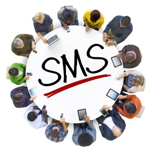 Group of People Holding Hands Around Letter SMS