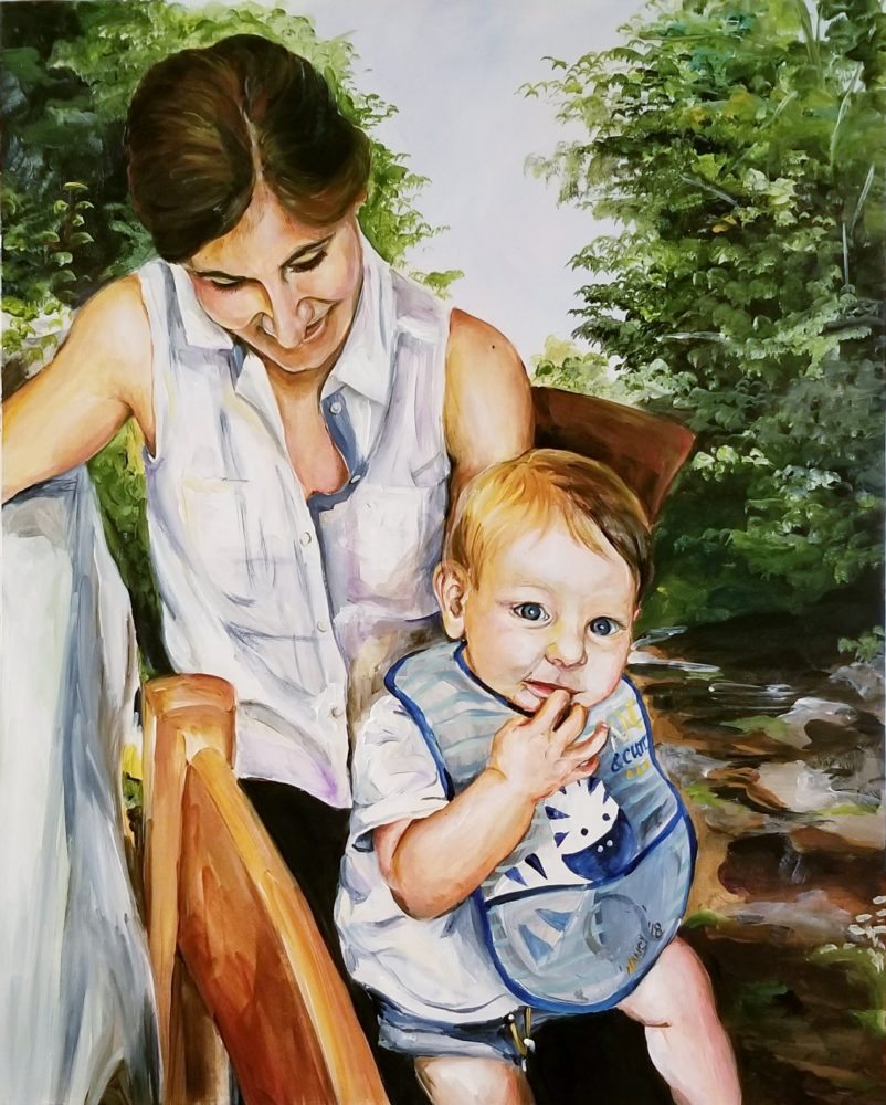 A young mother in a white sleeveless shirt holds her one year old baby boy on her lap with woods and a stream behind her.