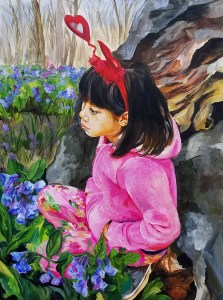 A little girl with straight black hair cut in a bob, a red heart head-band, dressed in pink floral pants and a pink fleece goodie, kneels against rocks in a field of wild bluebells.