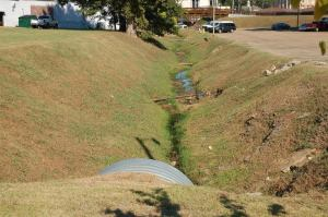 This photograph shows the current open storm sewer, viewed running east from Carter Avenue toward Main Street.