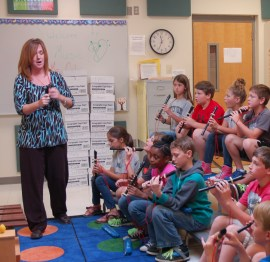 Music teacher Celia House shows NAES students the proper way to hold a recorder.