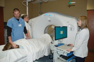 Radiologist Dr. Jeffery O'Rear MD, CT Tech Candy Hill and Tech Laura Williams demonstrate cat scan equipment with Baptist employee Chelsey Hall posed as a patient.