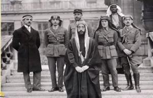 Prince Faisal (front), T. E. Lawrence (middle row, second from right), and Faisal's black slave bodyguard (top of frame) posed during the Paris Peace Conference in 1919.