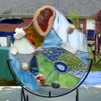 Art piece by Carol Lybanon, of Memphis, who incorporates fossils and stained glass in her abstract pieces.
