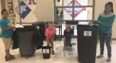 "Students from Mrs. Christy Pipkin's 4th grade class demonstrate the correct steps for recycling plastic milk containers. (L-R) Jesus Pedraza places trash in the trash bin; Laken Hopkins demonstrates putting the milk tops in the ""Tops"" bin; Kyle Wommack pours out leftover milk in the ""Waste"" bin; and A'Treszer Freeman prepares to put the empty milk bottle in the ""Plastic"" bin for recycling."