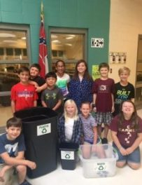"Students from Mrs. Ninabeth Capaning's EXCEL class get bins ready in the cafeteria for ""Recycling Wednesdays."" Standing left to right: Jeb Bolen, Gregory Nelson, Mac Blackburn, Riley Blackard, Casey Hernandez, Will Hefner, and Mack Wallis. Kneeling left to right: Mason Keener, Lela Trout, Maggie Ann McNutt, and Nicole Strockbine"