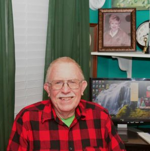 Joe Wilson at his computer. Photograph above his left shoulder is of Greta, his wife of 60 years.