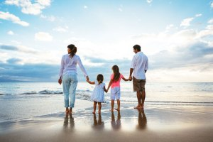 Home page main image of a family with two children on a beach at sunset