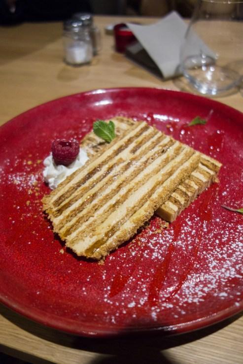 medovik : biscuit au miel et ganache à la confiture de lait sur une assiette rouge