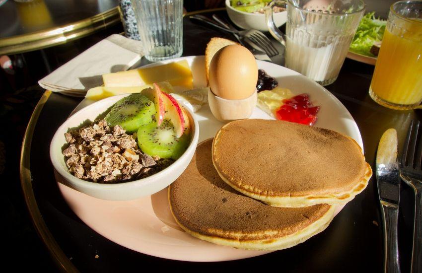 muesli au fruits, pancakes, oeuf dur et fromage