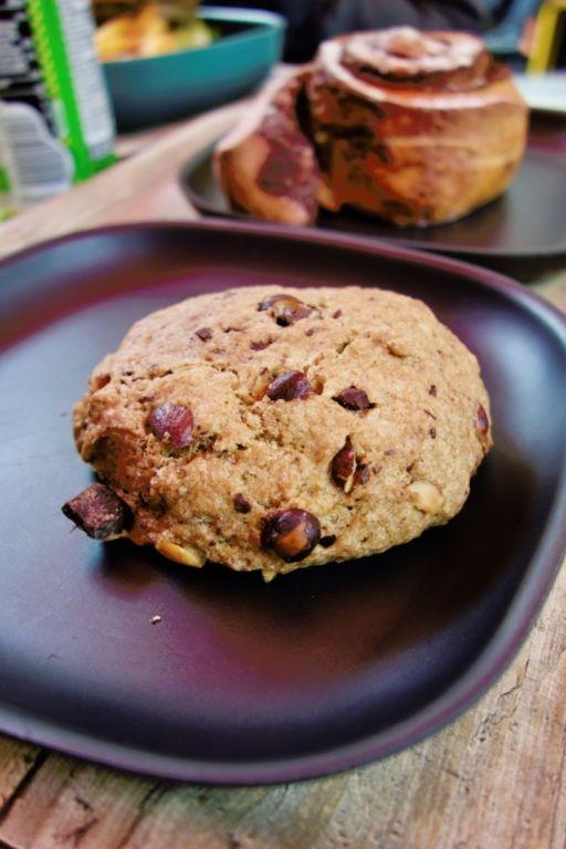 grand cookie vegan aux noisettes dans une assiette noire