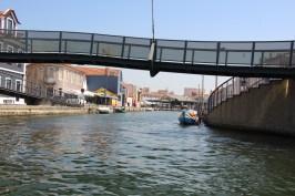 Ponte pedonal circular permite atravessar 2 canais. Ao fundo a Praça do Peixe