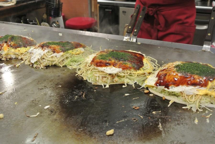 Finishing off each pancake by brushing on okonomiyaki sauce and aonori (seaweed flakes).
