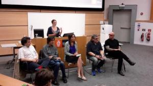 This image shows writers Frédéric Grellier, Romain Villet, Naomi Foyle, Rod Michalko and Ryan Knighton sitting on chairs arranged in a row in front of a long computer podium. Hannah Thompson is standing behind the podium, addressing the auditorium audience.