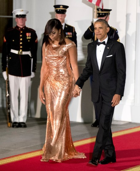 President Barack Obama and first lady Michelle Obama walk to North Portico at the White House to greet Italian Prime Minister Matteo Renzi and his wife Agnese Landini, for a State Dinner at the White House in Washington, Tuesday, Oct. 18, 2016. The first lady is wearing a floor length, rose gold chainmail gown designed by Atelier Versace. (AP Photo/Manuel Balce Ceneta)