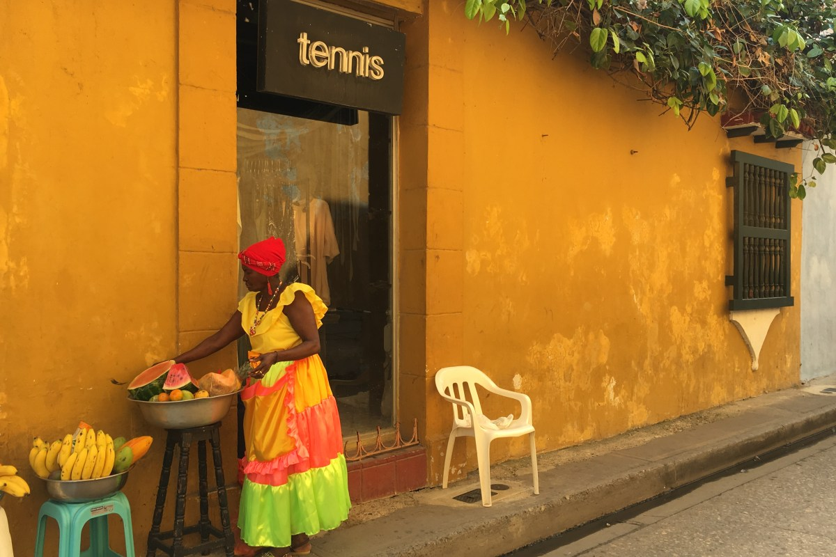 palenquera in bright colored traditional dress and red head wrap in front of aged yellow wall in Cartagena. Her rich brown skin pops against and wall and she is cutting watermelons and fruit.