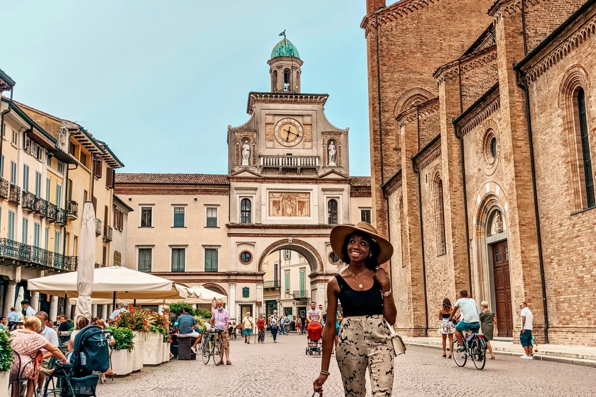 Image of Girl walking in Crema with Watchtower Behind her. Light blue sky, Cathedral on Right