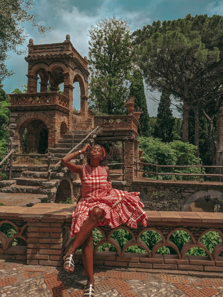 woman sitting in front of garden in red check dress