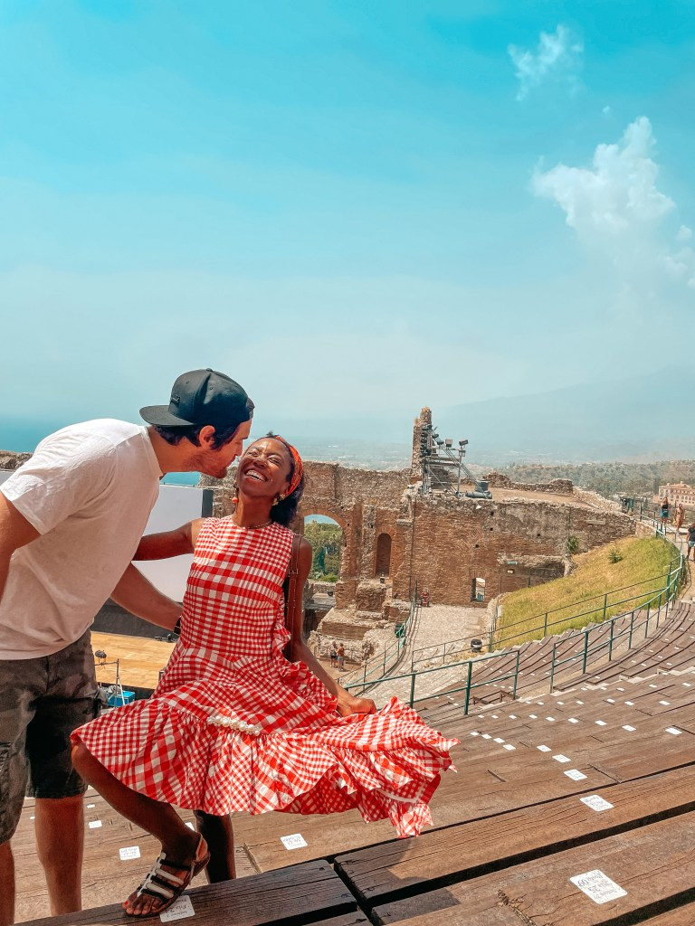 man and woman kissing in front of ancient Greek and Roman theatre. Woman in red check dress