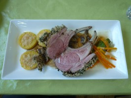 Herb crusted lamb with polenta and braised vegetables.