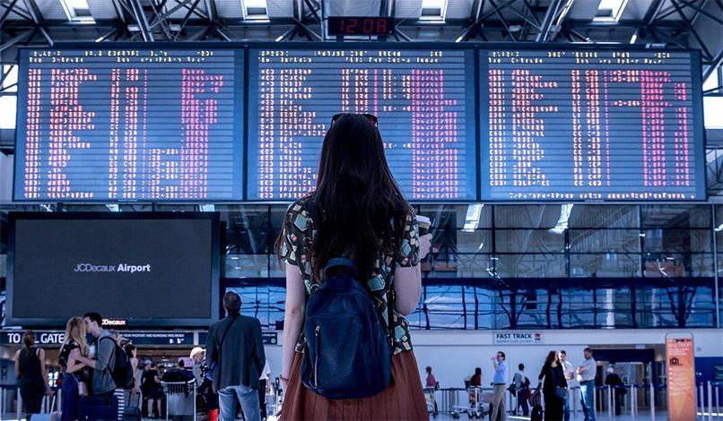 woman looking at airport flight board