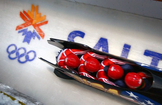 (Right to left) Pilot Brian Shimer, World Class Athletes SPECIALIST Mike Kohn, USA, and SPECIALIST Doug Sharp, USA, with brakeman Dan Steele speed down the track at Utah Olympic Park in Park City, Utah, during the second heat of the men's four-man bobsled in the 2002 WINTER OLYMPIC GAMES, 02/22/2002. NARA ID: 6527766