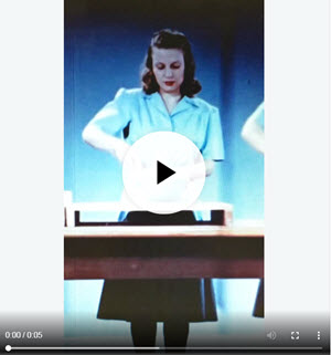 """Still from """"A Step Saving Kitchen,"""" GIF, showing a woman stirring a bowl, with an overlaid play button and video status bar."""