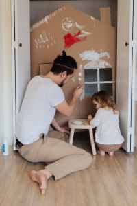 man in white t shirt and brown pants painting cardboard house, ouderverstoting