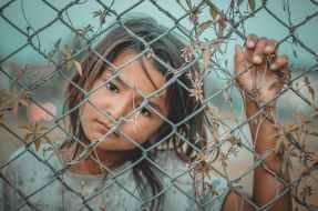 girl s white and gray crew neck top holding gray wire fence, Ondersteunende communicatie in de begeleiding van kwetsbare mensen