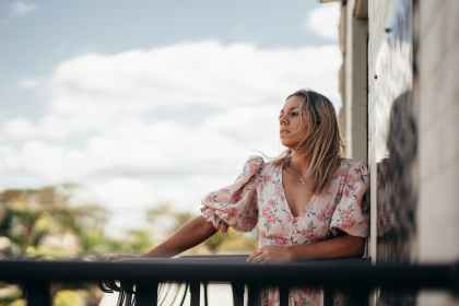 woman in summer dress admiring street in balcony