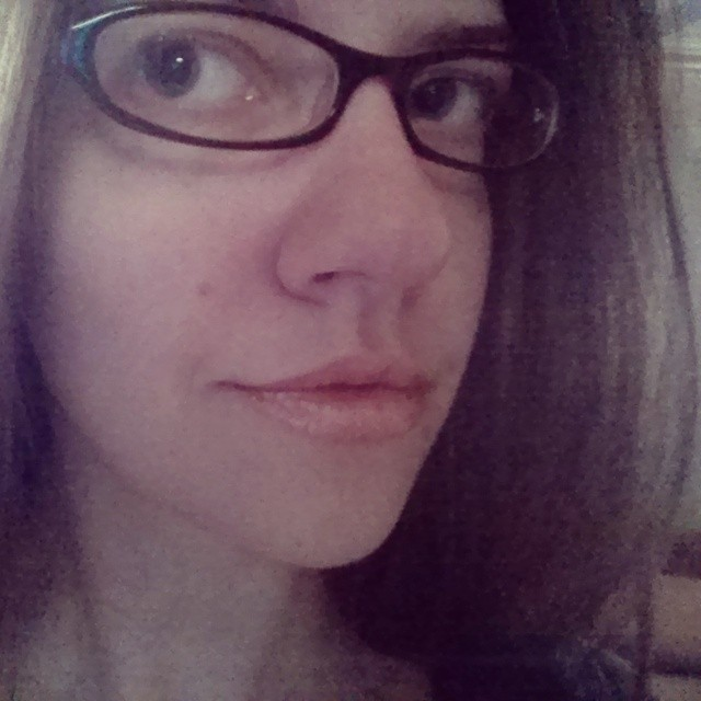 a closeup photo of laurel green smirking and wearing glasses