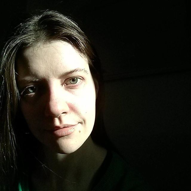 a high-contrast photo of laurel green smiling evilly