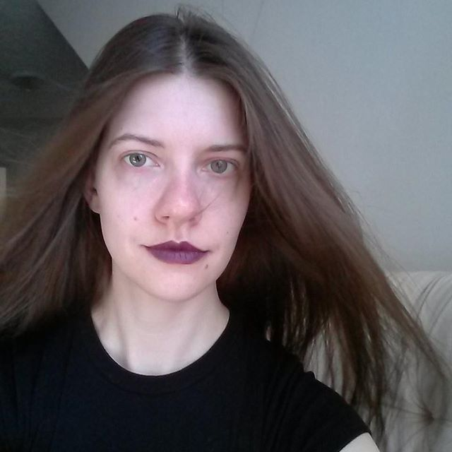 a photo of laurel green looking goth and have wind blow through her hair