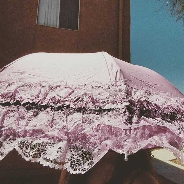 photo of laurel green hidden by a pink sun umbrella