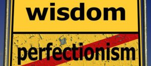 "sign that says ""wisdom and ""perfectionism"" crossed out"