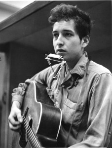 "NOVEMBER 1961:  Bob Dylan recording his first album, ""Bob Dylan"", in front of a microphone with an acoustic Gibson guitar and a harmonica during one of the John Hammond recording sessions in November 1961 at Columbia Studio in New York City, New York. (Photo by Michael Ochs Archives/Getty Images)"