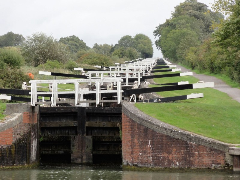 Photograph looking up the flight of 16 locks at Caen Hill. You can see row after row of gate beams like some '60s album cover.