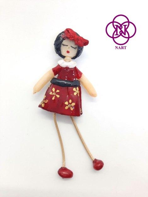 Broche muñequita roja detalle