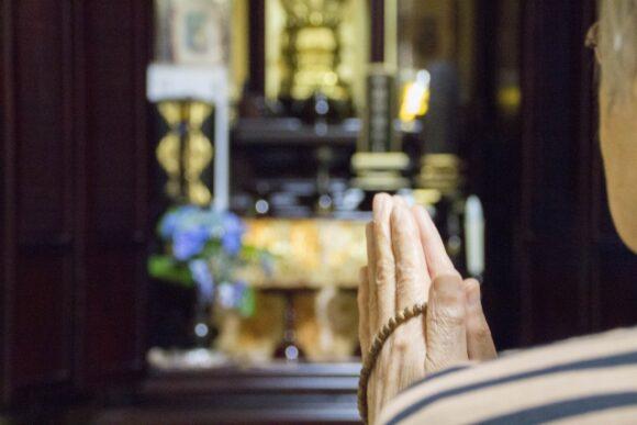 仏壇の前で読経をあげる僧侶