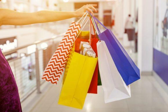 買い物袋をたくさんぶら下げる女性