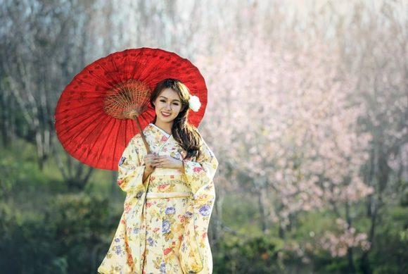赤い和傘をさす着物の女性