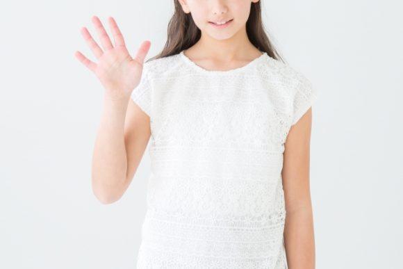 右手を上げる白い服の女性