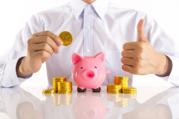 豚の貯金箱にお金を貯める男性