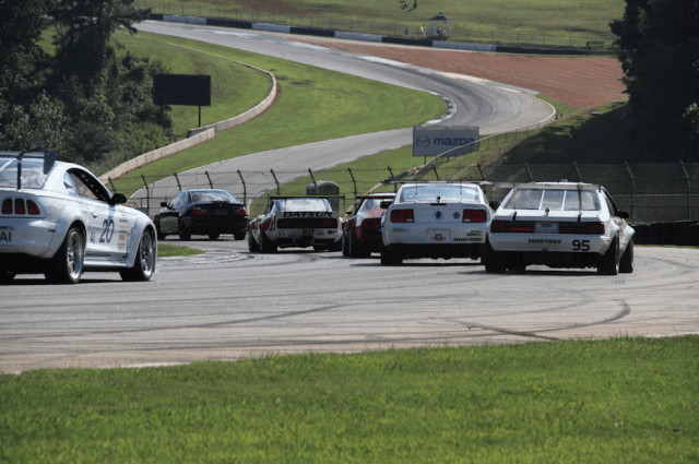 "American Iron and Outlaw Vintage cars head down into ""Gravity's Cavity,"" the downhill portion of the esses at Road Atlanta."